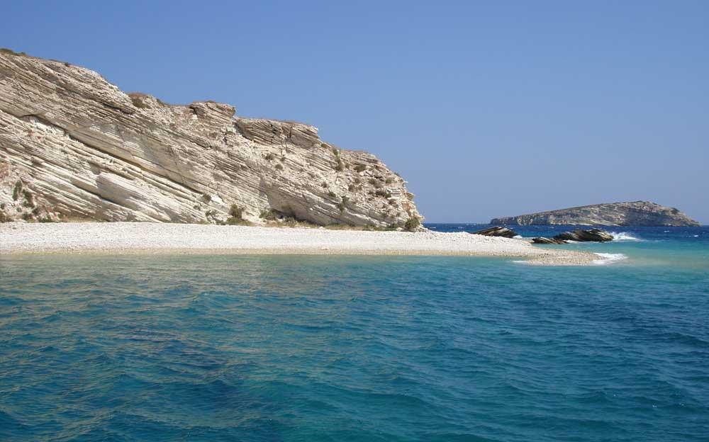 Eine Insel mit einem markanten Felsen und Kieselsteinstrand. Im Hintergrund ist eine weitere Insel zu sehen.
