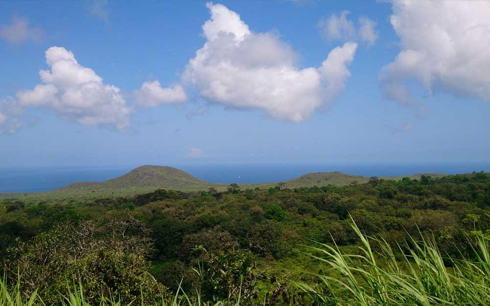 Grüne Hügel auf der Insel San Cristobal mit weissen Wolken am Himmel und dem Meer im Hintergrund.