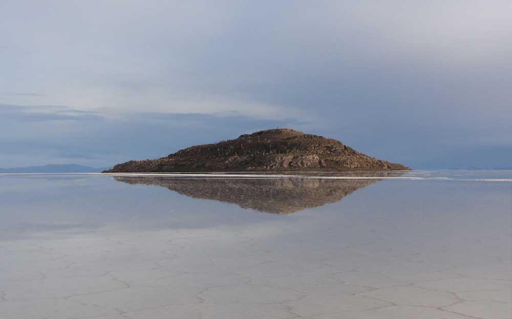 Eine kleine Insel spiegelt sich im Meer. Im Vordergrund ist das seichte Wasser.