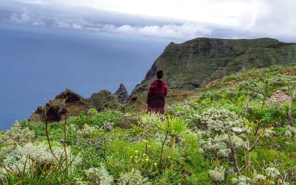 Eine indigene Frau steht in Südamerika auf einer Klippe und blickt aufs Meer hinaus.