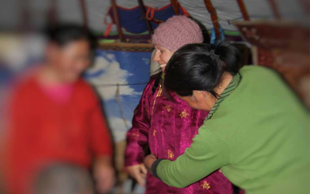 Energietherapeutin Manuela Krah zu Gast im Zelt bei einem Naturvolk in der Mongolei. Sie probiert ihren neuen, fuchsiaroten Mantel an, den sie bei den Gastgebern gekauft hat.