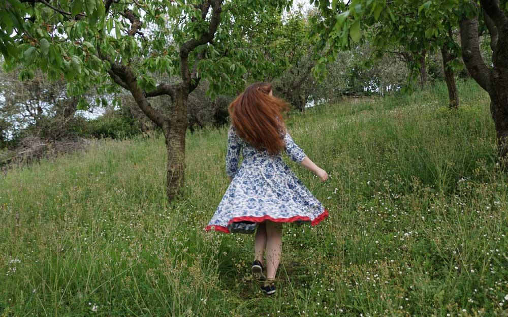 Energietherapeutin Manuela Krah tanzt in einem blau-weissen Sommerkleid mit markantem rotem Saum auf einer Wiese zwischen Bäumen hindurch,