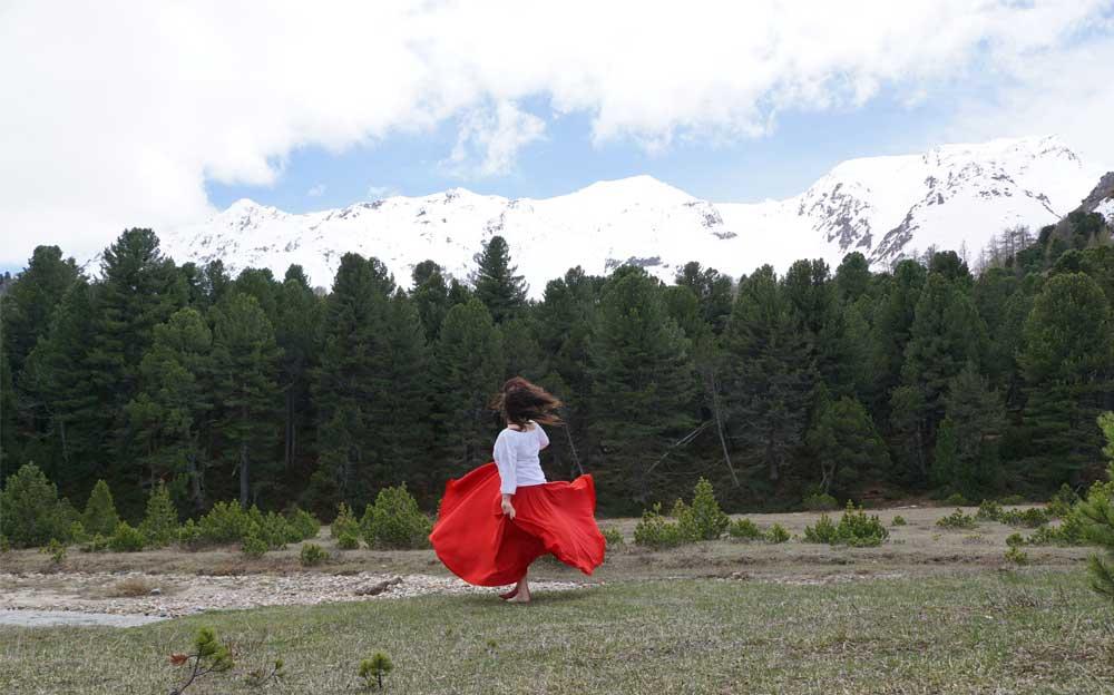 Energietherapeutin Manuela Krah tanzt in einem roten Rock und weisser Bluse neben einem Bach. Im Hintergrund sind dunkelgrüne Tannen und dahinter weisse Schneeberge zu sehen.