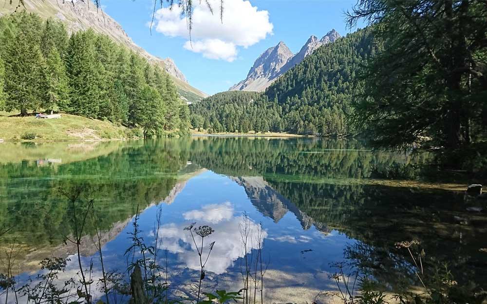 Bergsee, in dem sich die Wolken und der Himmel spiegeln. Im Hintergrund Berge. Links und rechts stehen Tannen um den See. Links eine kleine Halbinsel mit einer Sitzbank.