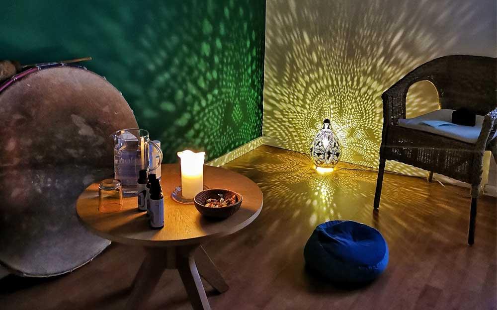Das Behandlungszimmer der Energietherapeutin Manuela Krah. Eine grosse indianische Trommel steht an einer Wand. Eine Laterne wirft ein Muster an die hintere gelbe Wand und an die grüne Wand links im Vordergrund.