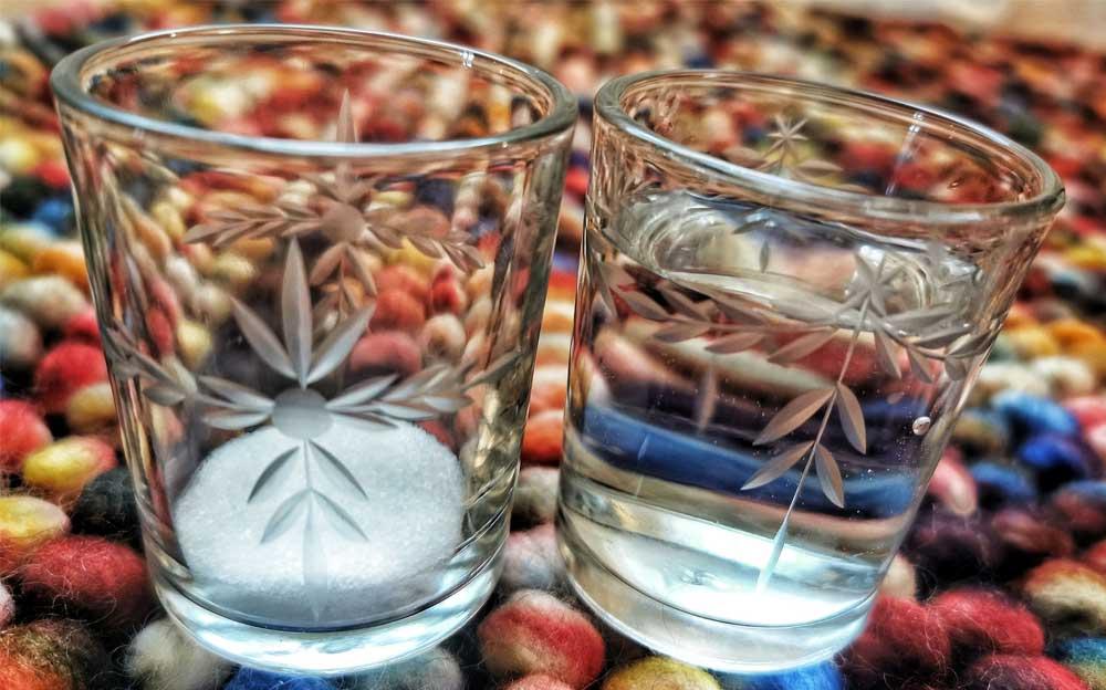 Zwei Gläser mit spirituellen Zeichen. Das Glas links ist leer. Das Glas rechts ist mit Wasser gefüllt.