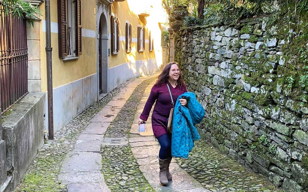 Die Energietherapeutin Manuela Krah schreitet über einen Weg mit Kopfsteinpflaster in Isola San Giulio Lago d'arta, Italien. Sie trägt eine hellblaue Jacke über dem Ärmel.
