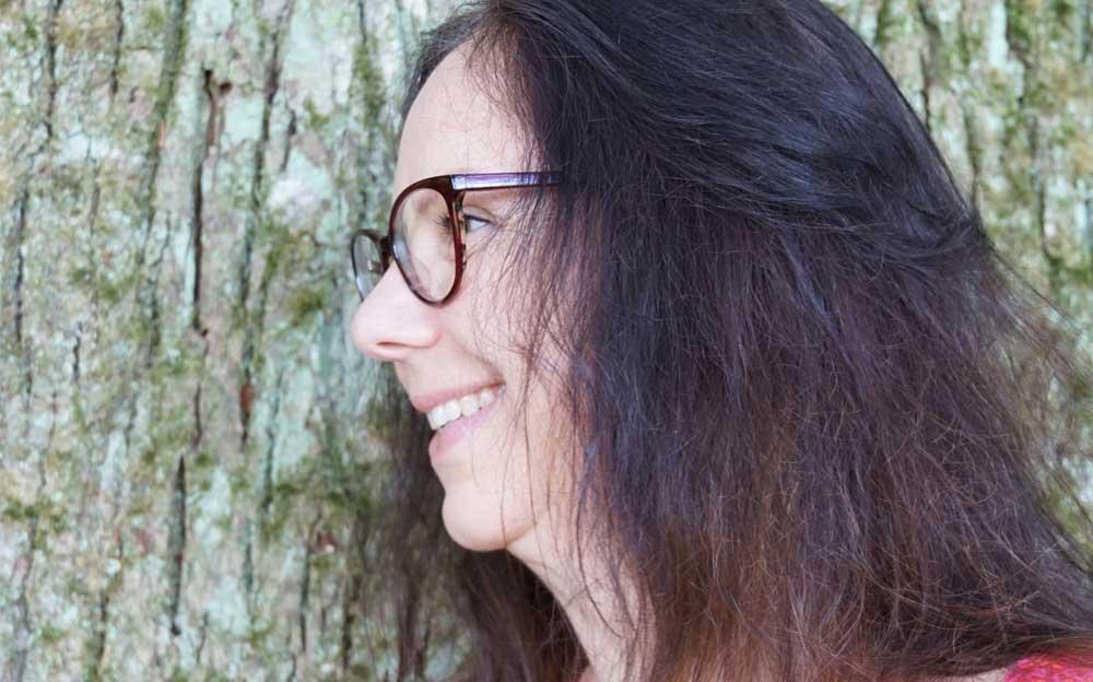 Seitenaufnahme der Energietherapeutin Manuela Krah. Sie steht vor einem Baum, hat schulterlange dunkelbraune Haare und trägt ein rotes Shirt mit Ornament-Muster.