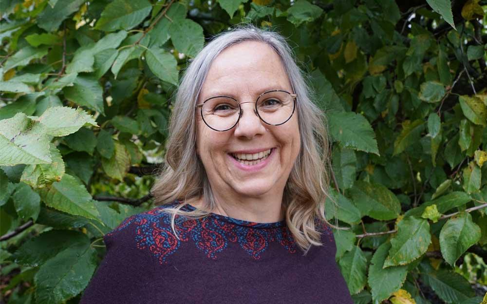 Porträt der Energietherapeutin Manuele Krah. Sie steht vor einem grünen Strauch und hat schulterlange graue Haare. Sie trägt eine feine, grosse Brille mit schwarzen Rändern.