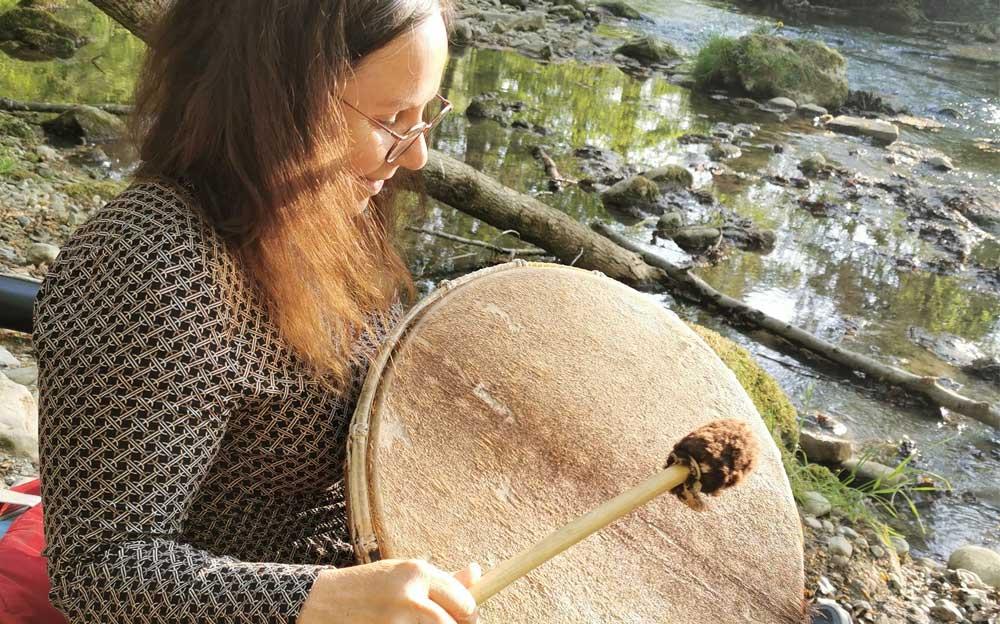 Die Energietherapeutin Manuela Krah sitzt am Ufer eines Baches auf Steinen. In der rechten Hand hält sie einen Schlägel. Damit schlägt sie auf ihre schamanische Trommel.