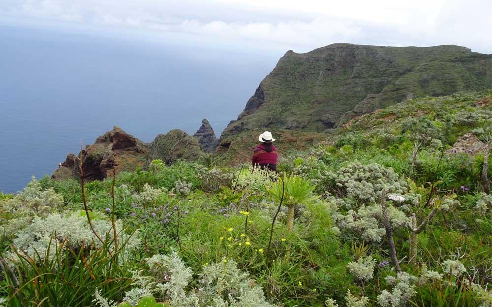 Die Energietherapeutin Manuela Krah sitzt auf einer grünen, dichtbewachsenen Klippe und schaut aufs Meer hinaus. Sie trägt einen weissen Panama Hut und einen roten Umhang, wie er typisch für die indigenen Völker Südamerikas ist.