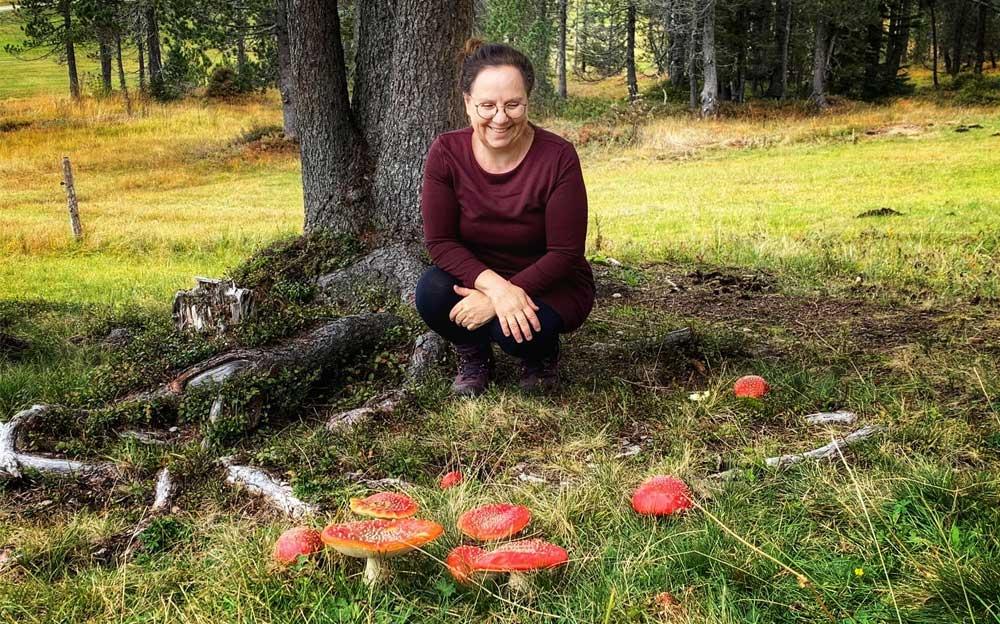 Die Energietherapeutin Manuela Krah kauert vor einem Baum am Boden und sieht sich grosse Fliegenpilze an.