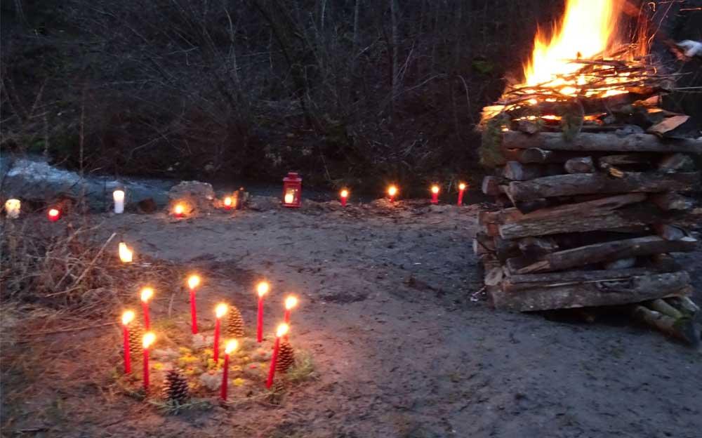 Ein sorgfältig aufgebauter Holzhaufen brennt. Zwischen dem Holz befinden sich die Steine für die Schwitzhüttenzeremonie. Links im Vordergrund ist ein Kreis mit brennenden, roten Kerzen zu sehen. Im Hintergrund ist der Wegrand mit brennenden Kerzen und Laternen markiert.