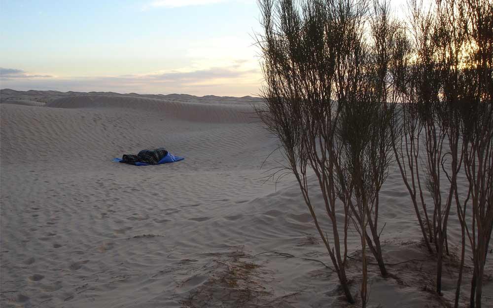 Die Energietherapeutin Manuela Krah liegt in einem blauen Schlafsack in der Sahara. Im Hintergrund links sind Hügelzüge; im Vordergrund rechts Sträucher zu sehen.