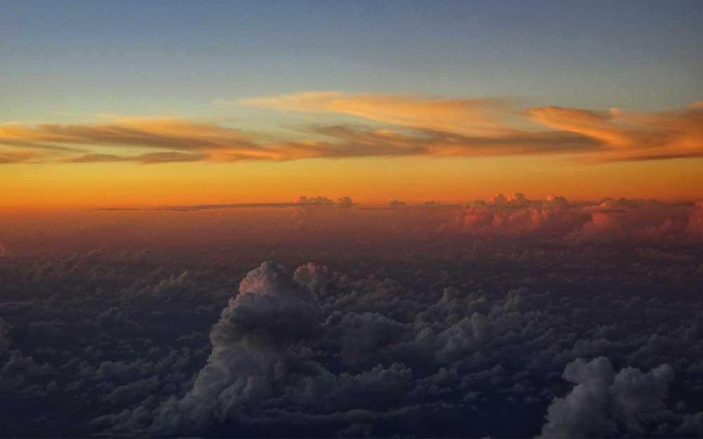 Wolken in der Dunkelheit. Im Hintergrund ein gelb-oranger Streifen der aufgehenden Sonne und darüber der blaue Himmel.