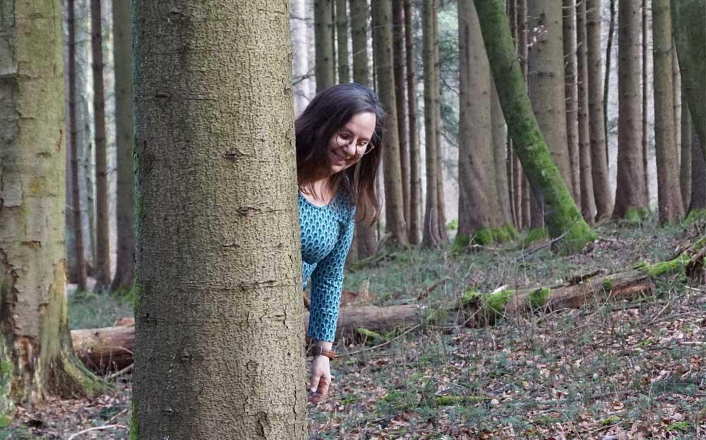 Energietherapeutin Manuela Krah steht im Wald und blickt hinter einem Baum hervor.