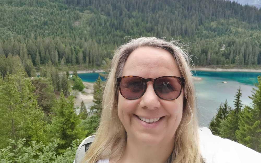 Manuela Krah steht mit einer Sonnenbrille vor Wald und Hügel. Der Wald geht um den Caumasee herum.