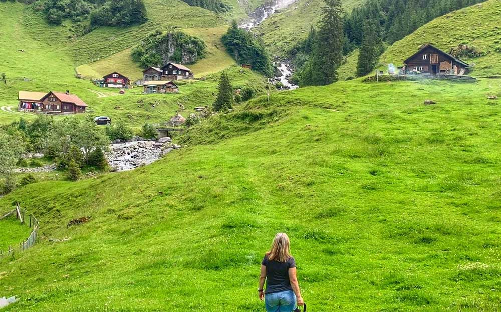 Manuela steht am Fusse eines kleinen Bergdorfes und schaut auf einen Wasserfall.