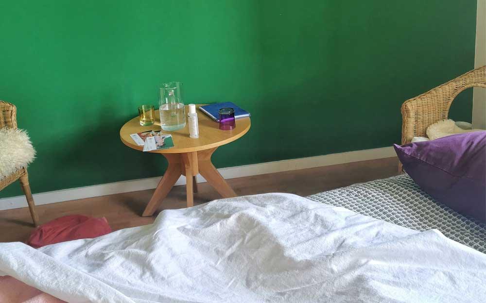 Neben einer Liege mit 2 dünnen Decken darauf steht ein Holztischchen mit 2 Stühlen. Dahinter an der grünen Wand hängt eine gelbe Sonne.