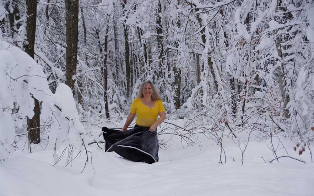 Manuela Krah steht kniehoch im Schnee und tanzt im Wald.