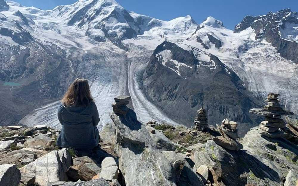 Frau sitzt auf einem Stein vor Bergpanorama