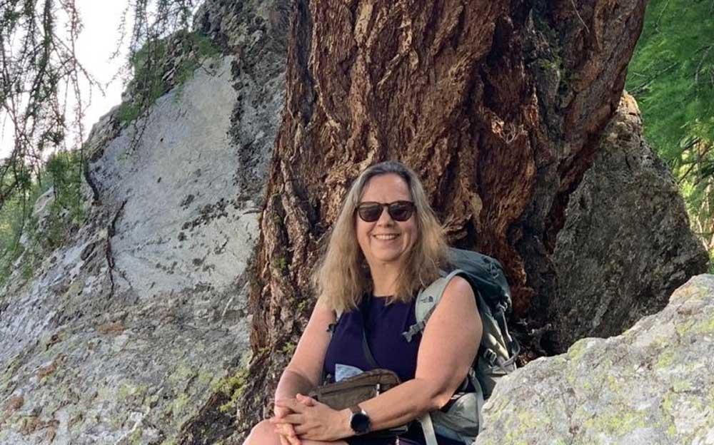 Manuela Krah sitzt im Wald vor einem Baum und lacht in die Kamera.