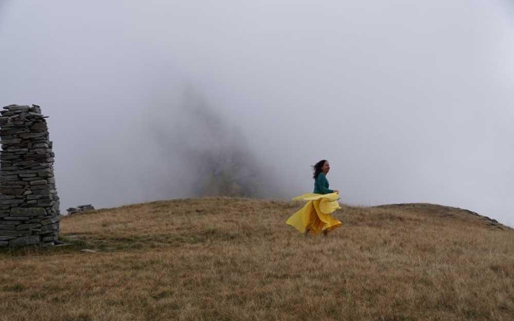 Manuela Krah läuft in einem wallenden gelben Kleid über eine trockene Wiese. Im Hintergrund ist Nebel zu sehen.