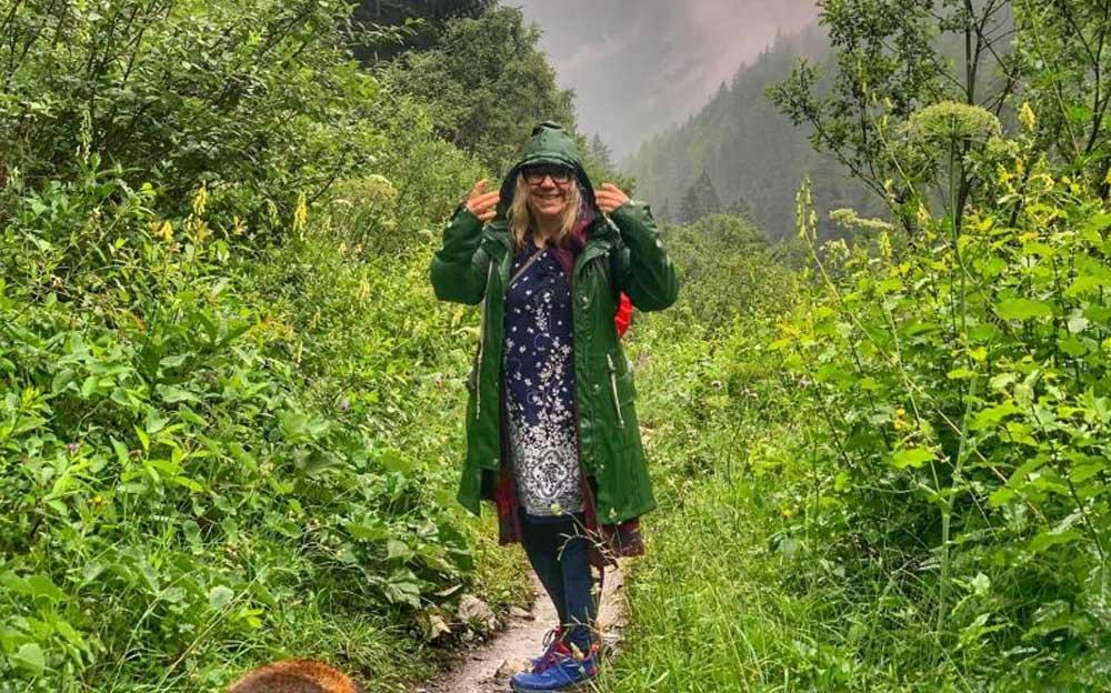 Manuela Krah steht in einem Regenmantel auf einem Wanderweg mitten in einem grünen Wald.