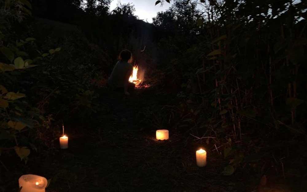 Schwitzhütte in der Dunkelheit. man sieht nur das Kerzenlicht auf dem Weg zur Schutzhütte im Wald.
