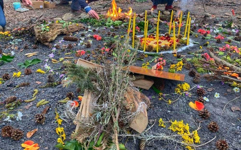 Buntes Mandala aus Blüten und Kerzen auf dem Waldboden.