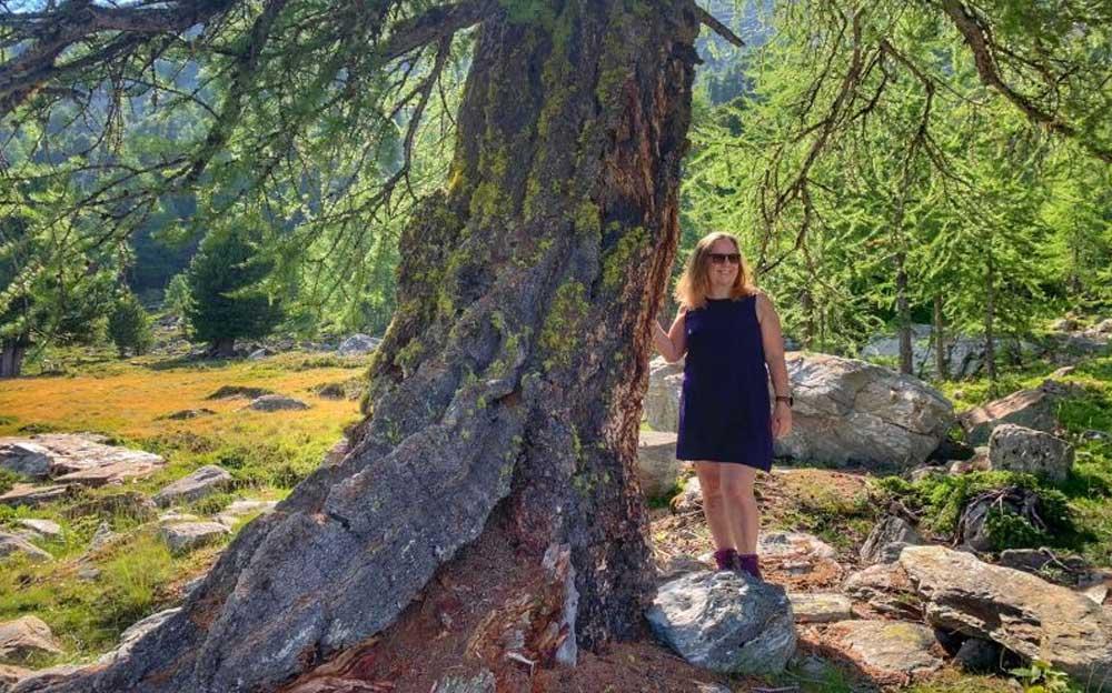 Manuela Krah steht neben einem Grossen Baum in neben einer Sonnendurchfluteten Waldlichtung.